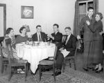 Players performing a dining room scene.