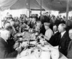 Men and women having a meal under a tent