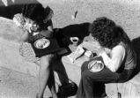 Two female students eating lunch outside.