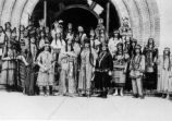 People in Native American dress in front of Tower Hall.