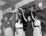 Teenage girls check paper aircraft