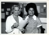 Elaine Mitchell and another woman in front of the YWCA's bulletin board