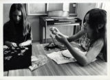 Two girls working on fabric crafts