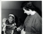 Woman looking at a little girl with two dolls
