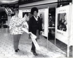 Elaine Mitchell and another woman walking past YWCA posters