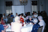 Women at dining tables listening to a speaker