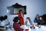 Woman addressing women sitting at dining tables.