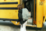 Child walking next to a school bus