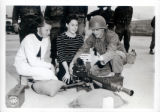 Photograph of a soldier and two girls with a machine gun and a descriptive note