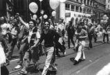 Parade participants carrying balloons.