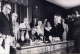 Patricia Whiting and other legislators look on as Governor McCall signs a bill
