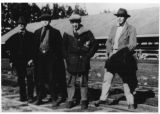 John Steinbeck with three others standing on railroad tracks